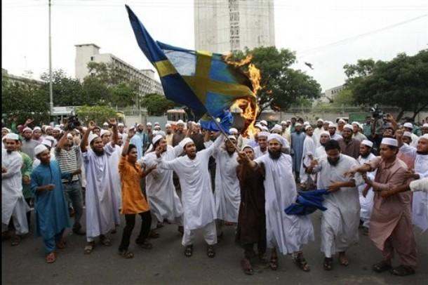 Bangladeshi Muslim protesters shout slogans as they burn a Swedish flag during a protest against social networking website facebook for holding a competition on caricatures of Prophet Mohammed, in Dhaka, Bangladesh, Friday, May 28, 2010. According to news reports, Swedish artist Lars Vilks has angered many Muslims by drawing highly blasphemous caricature of the Prophet. (AP Photo/Pavel Rahman)